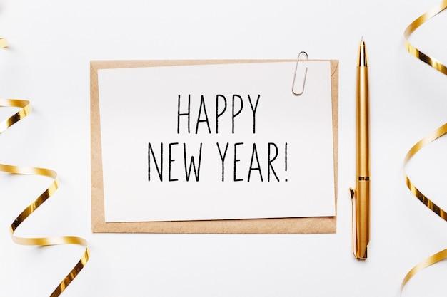 白い背景に封筒、ペン、ギフト、ゴールドリボンで新年あけましておめでとうございます。メリークリスマスと新年のコンセプト
