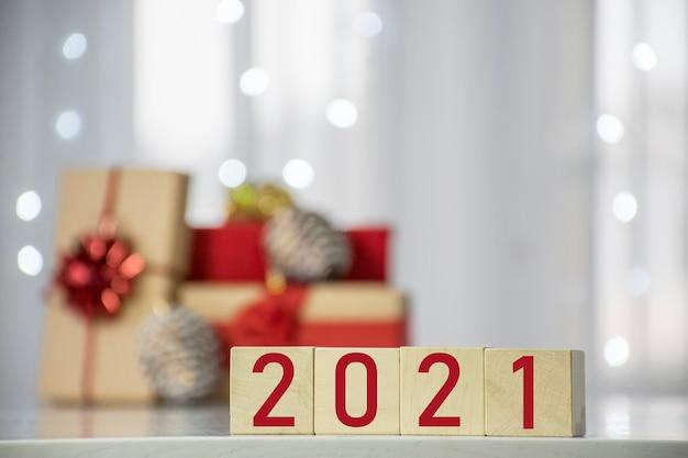 木製の立方体ブロックとギフトボックスとぼやけたボケライトで新年あけましておめでとうございます