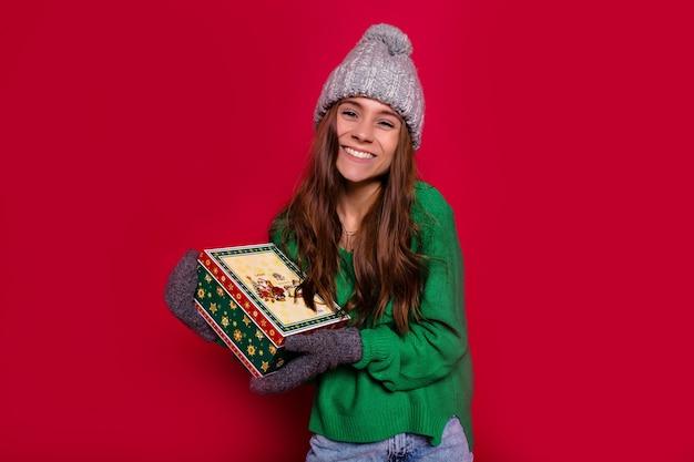 赤い背景のカメラにプレゼントを持って笑顔の素敵な若い女性の新年あけましておめでとうございます。かわいい笑顔、冬のプルオーバーとキャップ、楽しんで、誕生日のお祝い