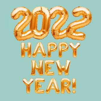 パステルミントの背景に金色の膨脹可能な風船で作られた新年あけましておめでとうございますフレーズ新年あけましておめでとうございますお祝いホイルのお祝いの装飾を形成するヘリウム風船