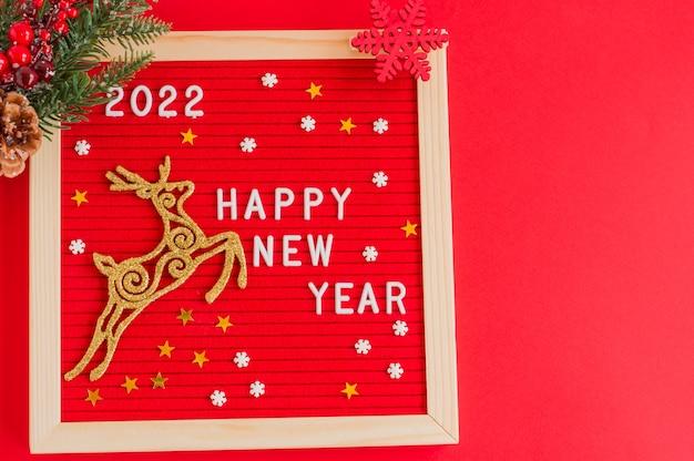 明けましておめでとうございます-フェルトのレターボードに引用してください。黄金の鹿とベリーとモミの枝とクリスマスのコンセプト。