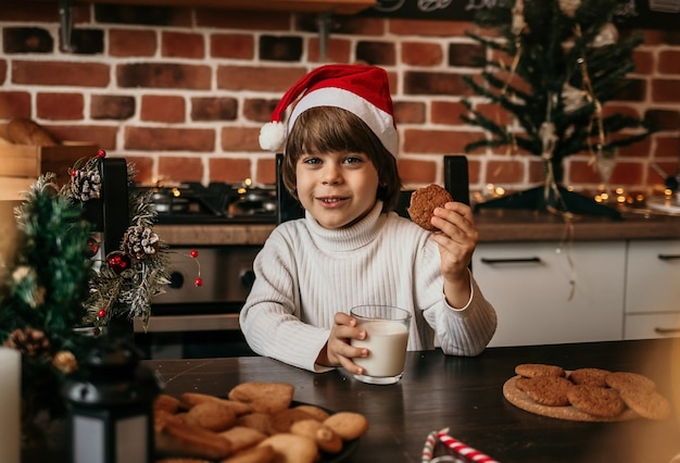A happy new year's boy is sitting at the kitchen table in a white sweater and a red new year's hat with milk and cookies