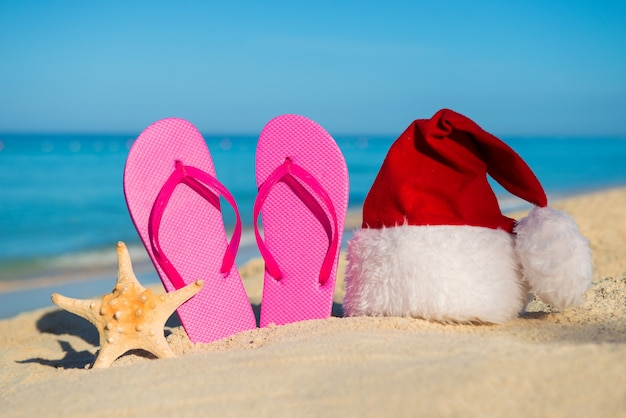 Happy  new year at sea. sandals and santa hat on sandy beach - christmas holiday concept