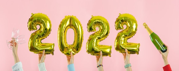 Happy new year. several hands holding numbers 2022 on pink background. copy space.
