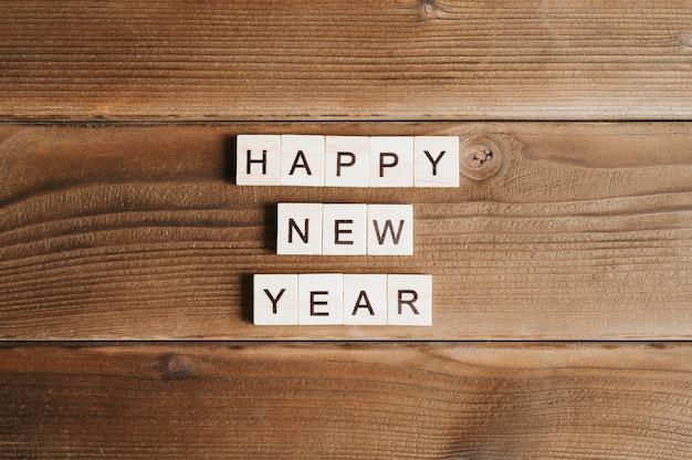 С новым годом текст деревянных квадратных букв на фоне стола деревянные доски