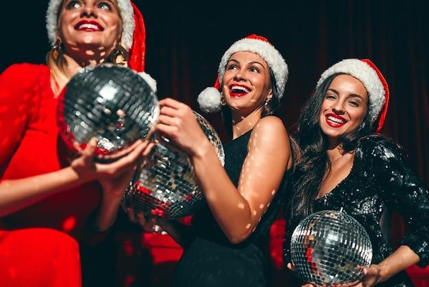 Счастливого тебе нового года! три красивых сексуальных женщины в шляпах санты с диско-шарами в руках. новогодний праздник. канун рождества.