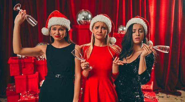 새해 복 많이 받으세요! 산타 모자를 쓴 세 명의 아름다운 섹시한 여성과 빈 안경이 뭔가 불만족 스러웠습니다. 새해 파티. 크리스마스 이브.
