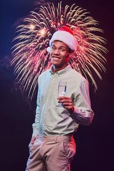 サンタクロースを身に着けている若い陽気な混血の男性の新年あけましておめでとうございます垂直ショット