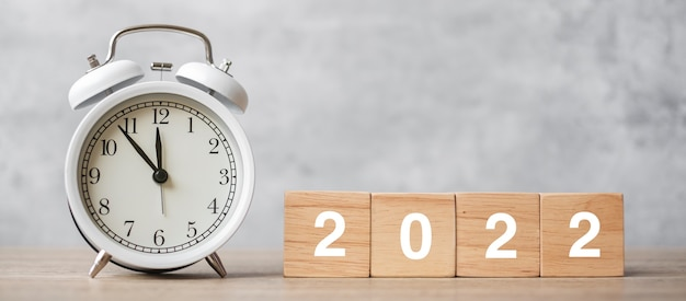 Happy new year with vintage alarm clock and 2022 block. christmas, new start, resolution, countdown, goals, plan, action and motivation concept