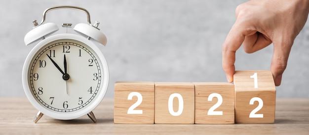 新年あけましておめでとうございます。ヴィンテージの目覚まし時計と手で2021を反転させて2022ブロックに変更します。クリスマス、新しいスタート、解決策、カウントダウン、目標、計画、行動、動機付けの概念
