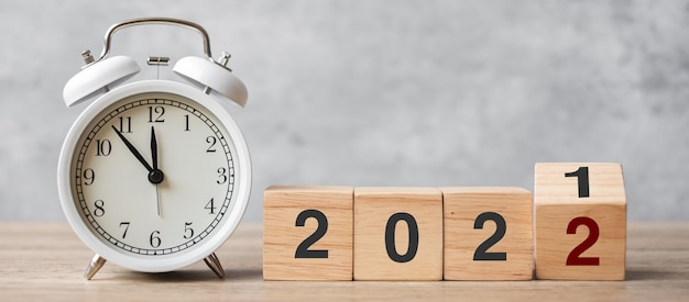 Happy new year with vintage alarm clock and flipping 2021 change to 2022 block. christmas, new start, resolution, countdown, goals, plan, action and motivation concept
