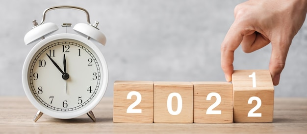 Happy new year with vintage alarm clock and hand flipping 2021 change to 2022 block. christmas, new start, resolution, countdown, goals, plan, action and motivation concept