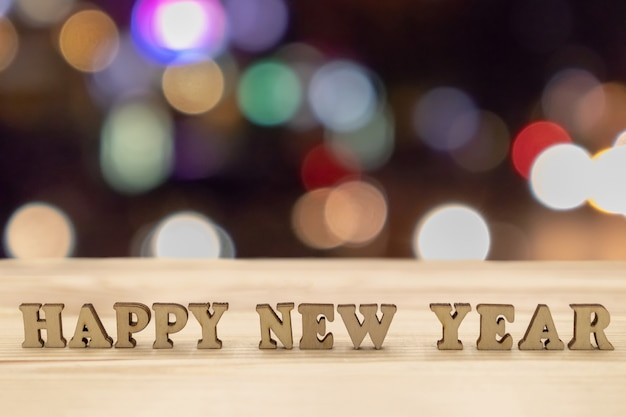 Happy new year on wood and blurred background