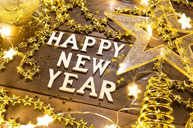 明けましておめでとうございます-スパンコール、星、花輪のライトでお祭りの背景に木製の文字。ご挨拶、はがき。