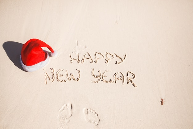 Happy new year written in the sand and santa hat on white sandy beach