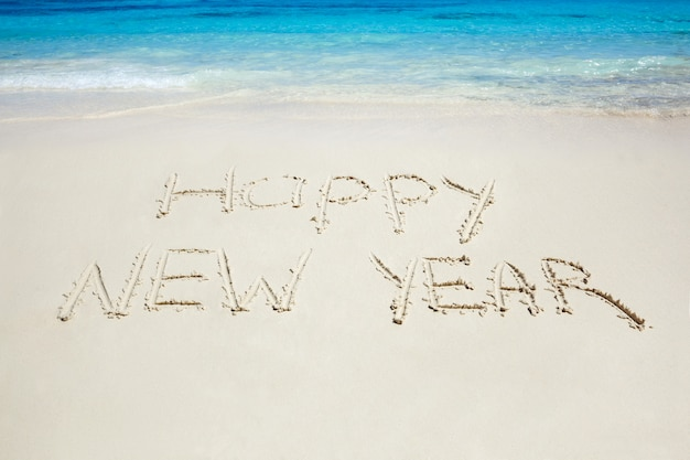 Happy new year written on sandy beach. tropical celebration. new year's tour