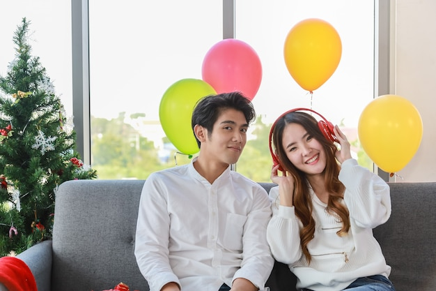 Happy new year, xmas and couple concept. asian young man and woman listen music with red headphone and sitting on sofa in christmas party