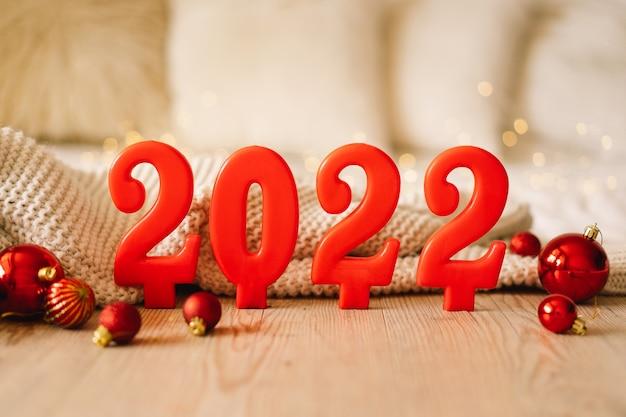ボケ味のお祭りのきらめく背景に赤いろうそくによって作られた新年あけましておめでとうございます年の数