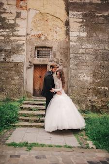 Счастливая пара новобрачных обниматься и целоваться на улице старого европейского города, великолепная невеста в белом свадебном платье вместе с красивым женихом. день свадьбы.