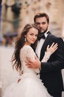 幸せな新婚カップルがハグし、古いヨーロッパの町の通りでキス