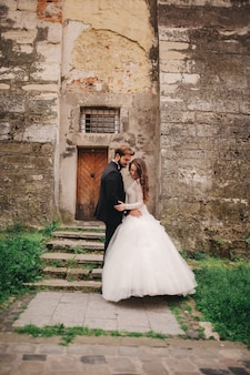 Happy newlywed couple hugging and kissing in old european town street, gorgeous bride in white wedding dress together with handsome groom. wedding day.