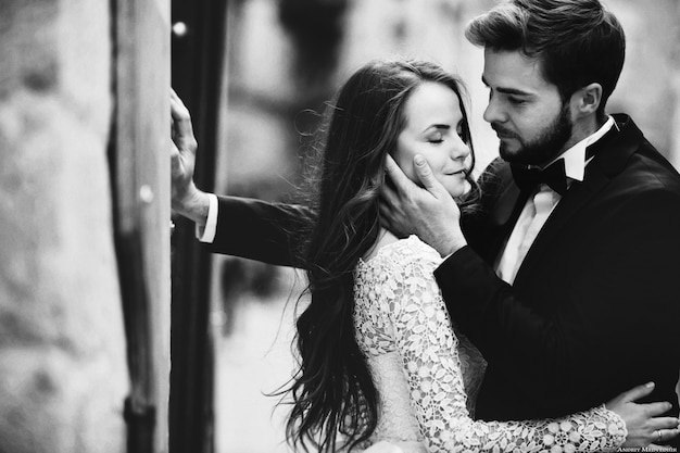 Happy newlywed couple hugging and kissing in old european town street Premium Photo