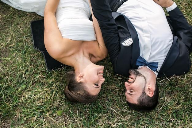 幸せな新婚夫婦草の上に横たわって、お互いを見て
