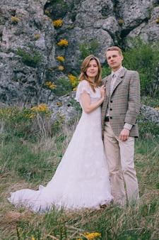 Happy newlywed couple near the rocks