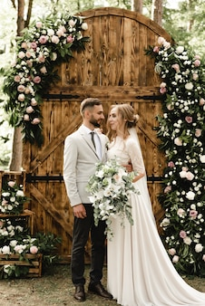 A happy newlywed couple posing with a wooden arch decorated with flowers