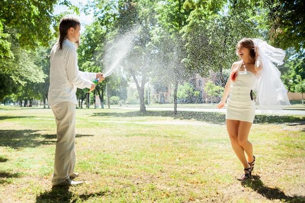 Счастливые молодожены празднуют свадьбу в парке