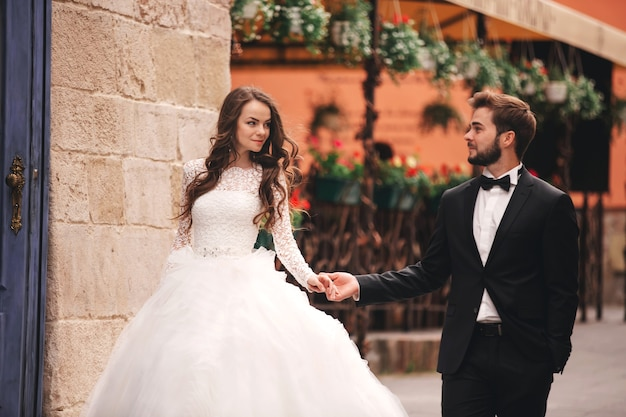 Happy newlyweds couple on a walk in old european town street, gorgeous bride in white wedding dress together with handsome groom.