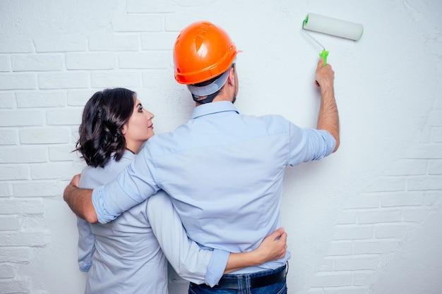 행복한 신혼 부부는 건설 헬멧 안전모를 쓴 잘생긴 남자와 집에서 흰색 벽돌 벽을 함께 그리는 매력적인 여자입니다. 주택 아파트에서 구매, 수리 및 건설의 개념