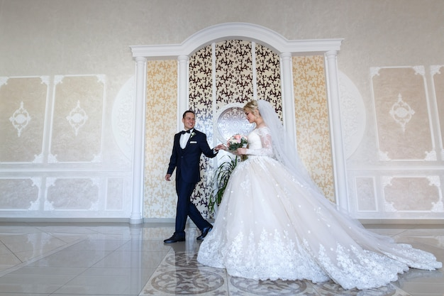 Happy newlyweds gently look at each other. smiling bride and groom gently hugging indoors in the white room. wedding couple in a wedding ceremony in a stylish interior. weeding day