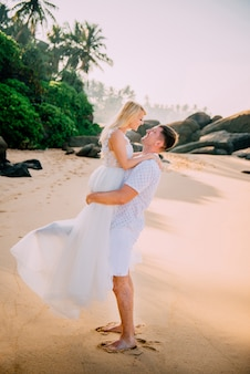 Happy newlyweds hugging against tropical beach background