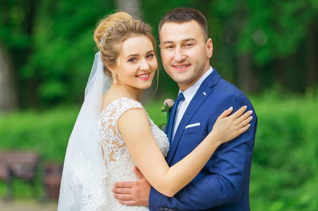 Счастливые молодожены обнимаются, красивое свадебное платье и стильный костюм. прогулка по парку.