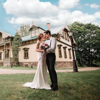 彼らの新しいシックな家の近くの幸せな新婚夫婦