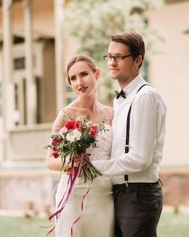 彼らの新しい家の背景に幸せな新婚夫婦