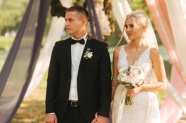 Счастливые молодожены на свадебной церемонии на улице только что поженились