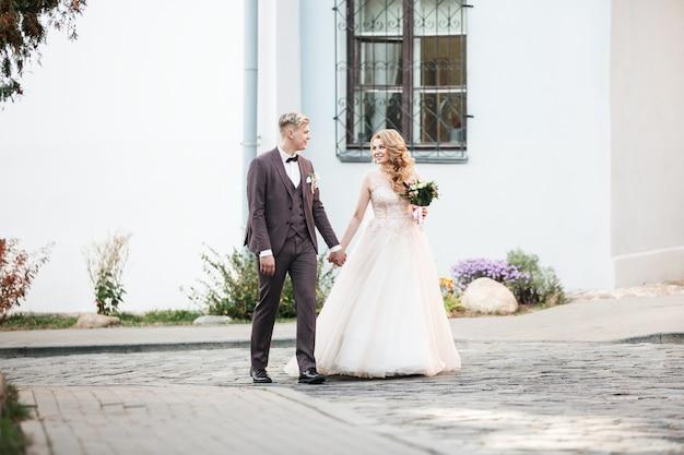 도시 거리를 지나가는 행복한 신혼 부부.