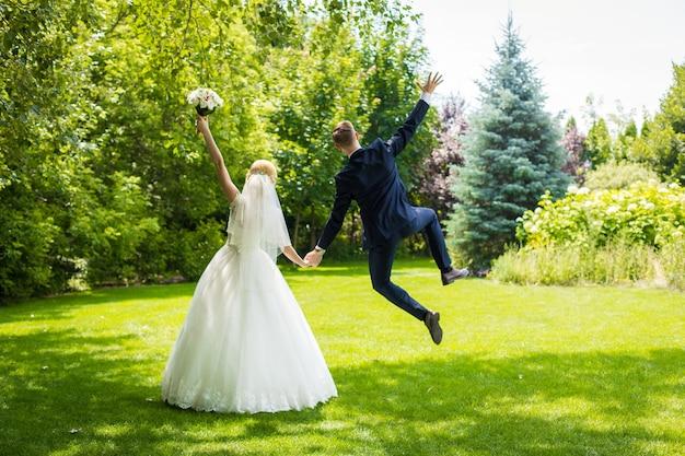 행복한 신혼 부부는 기뻐하며 녹색 잔디밭에 뛰어 듭니다. 아내 하얀 웨딩 드레스, 양복에 신랑.