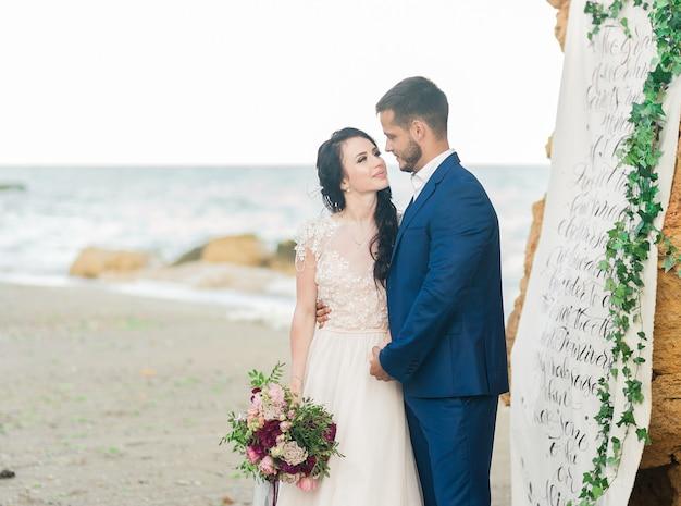 Счастливые молодожены стоят, взявшись за руки на фоне синего моря. свадебная прогулка по песчаному пляжу. на заднем плане голубое небо