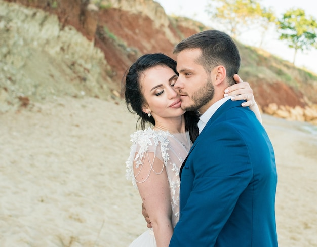 青い海の背景に手をつないで立っている幸せな新婚夫婦。砂浜での結婚式の散歩。背景には青い空