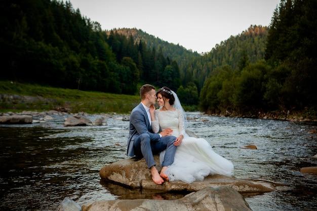 Счастливые молодожены стоя и улыбаются на берегу реки. молодожены, фото ко дню всех влюбленных.