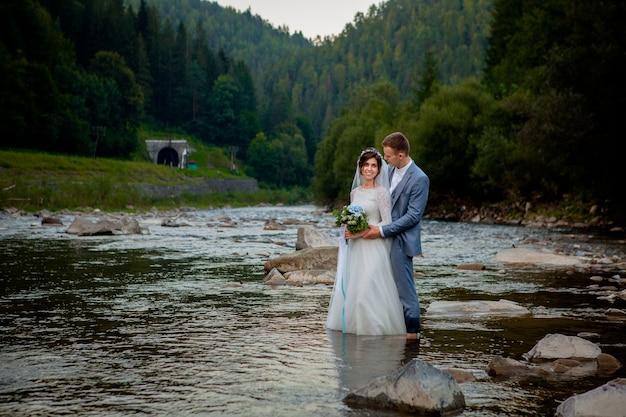 川に立って笑顔で幸せな新婚夫婦