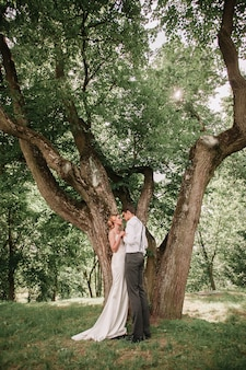 큰 확산 나무 근처에 서 행복 한 신혼 부부. 낭만적 인 순간