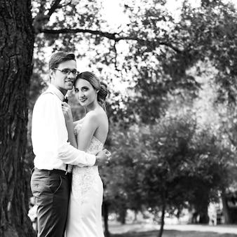 Счастливые молодожены, стоящие у городского озера. черно-белое фото