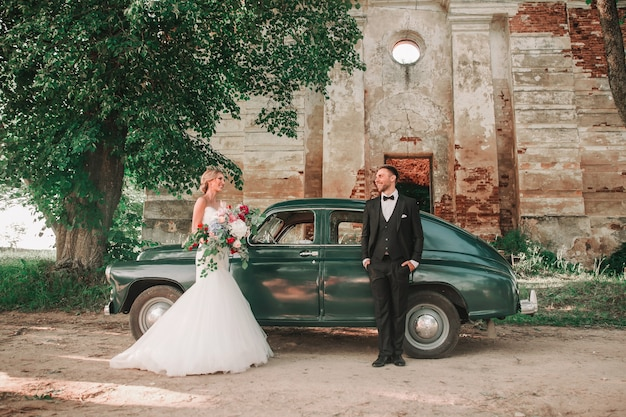 散歩中にスタイリッシュな車の横に立っている幸せな新婚夫婦。ウェディングウォーク