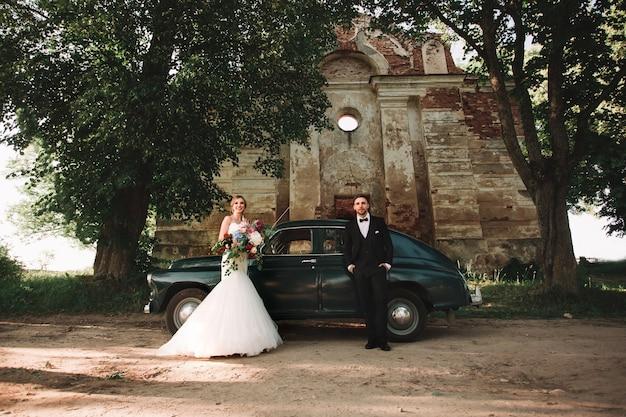 산책하는 동안 세련된 자동차 옆에 서 있는 행복한 신혼부부