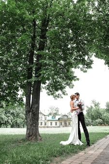 彼らの家の近くの芝生の上に立っている幸せな新婚夫婦。