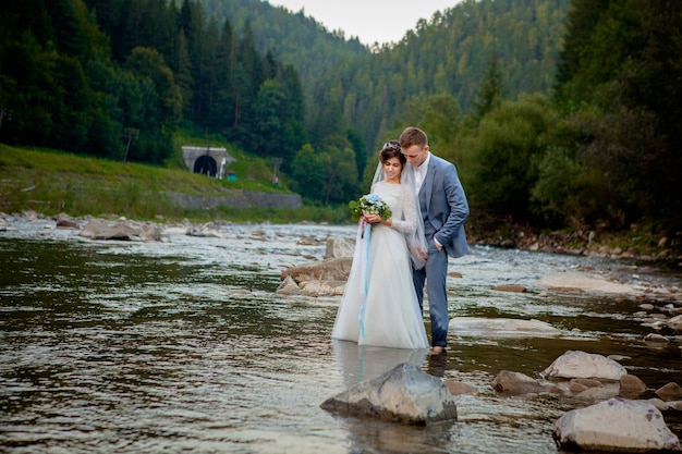 Happy newlyweds standing and smiling on the river . honeymooners, photo for valentine's day.